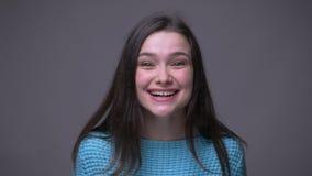 Close-upspruit van het jonge vrij donkerbruine vrouwelijke het glimlachen wordt opgewekt en het vieren bekijken camera met achter stock footage