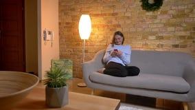 Close-upspruit van het jonge vrij Kaukasische vrouwelijke typen op de telefoon terwijl binnen het zitten op de bank stock video