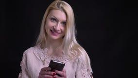 Close-upspruit van het midden oude Kaukasische vrouwelijke texting op de telefoon die camera bekijken en met achtergrond glimlach stock video