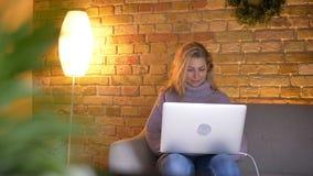 Close-upspruit van het volwassen Kaukasische aantrekkelijke vrouwelijke typen op laptop terwijl het zitten op de laag binnen in c stock video