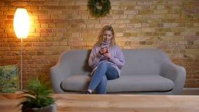 Close-upspruit van het volwassen Kaukasische blonde vrouwelijke texting op de telefoon terwijl het zitten op de laag binnen in co stock footage