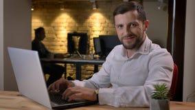 Close-upspruit van het volwassen Kaukasische zakenman typen op camera bekijken en laptop die cheerfully binnen binnen glimlachen stock afbeeldingen