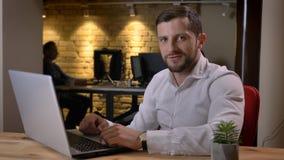 Close-upspruit van het volwassen Kaukasische zakenman typen op laptop die camera bekijken en binnen in het bureau glimlachen royalty-vrije stock fotografie
