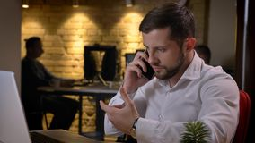 Close-upspruit van het volwassen Kaukasische zakenman typen op laptop en het hebben van formeel gesprek op de telefoon binnen bin stock afbeelding