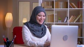 Close-upspruit van het volwassen moslim succesvolle onderneemster typen op laptop en het glimlachen met opwinding op de werkplaat stock videobeelden