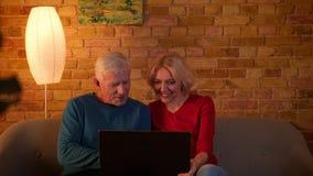Close-upspruit van hoger gelukkig paar die de laptop zitting op de laag binnen in een comfortabele flat gebruiken stock videobeelden