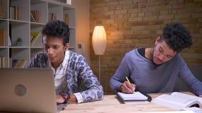 Close-upspruit van Indisch mannetje die aan muziek in vibes luisteren die laptop cheerfully en Afrikaanse Amerikaan gebruiken die stock videobeelden