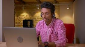 Close-upspruit van Indische jonge werknemer in hoofdtelefoons die een vraag hebben die laptop op de werkplaats in het bureau met  stock videobeelden