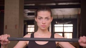 Close-upspruit van jong aantrekkelijk atletenwijfje die en klaar aan gewichtheffen in de gymnastiek binnen lopen worden stock video
