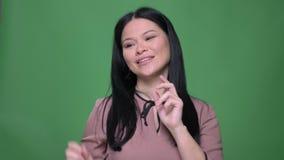 Close-upspruit van jong aantrekkelijk Chinees wijfje die verschillende gelaatsuitdrukkingen maken en pret voor hebben stock videobeelden