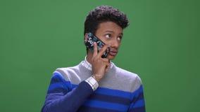 Close-upspruit van jong aantrekkelijk Indisch mannetje die die een telefoongesprek met achtergrond hebben op groen wordt ge?solee stock videobeelden