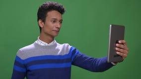 Close-upspruit van jong aantrekkelijk Indisch mannetje die die een videogesprek op de tablet met achtergrond hebben op groen word stock footage