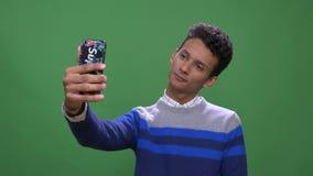 Close-upspruit van jong aantrekkelijk Indisch mannetje die die een videogesprek op de telefoon met achtergrond hebben op groen wo stock videobeelden