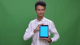 Close-upspruit van jong aantrekkelijk Indisch mannetje gebruikend de tablet en tonend het blauwe scherm aan camera met achtergron stock video