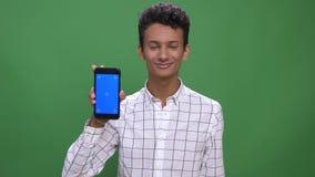 Close-upspruit van jong aantrekkelijk Indisch mannetje gebruikend de telefoon en tonend het blauwe scherm aan camera met ge?solee stock video