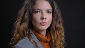 Close-upspruit van jong aantrekkelijk Kaukasisch vrouwelijk gezicht met donkerbruin krullend haar die camera met gevoelloos bekij stock foto's