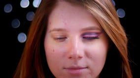 Close-upspruit van jong aantrekkelijk Kaukasisch vrouwelijk gezicht met half toegepaste make-up die recht camera bekijken stock videobeelden