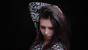 Close-upspruit van jong aantrekkelijk Kaukasisch vrouwelijk model die en voor de camera met achtergrond glimlachen stellen stock video