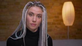 Close-upspruit van jong aantrekkelijk Kaukasisch wijfje met blonde die dreadlocks camera binnen in een comfortabele flat bekijken stock footage
