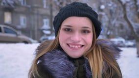 Close-upspruit van jong aantrekkelijk Kaukasisch wijfje met donkerbruin en haar die vreedzaam en opgewekt terwijl glimlachen zijn stock videobeelden