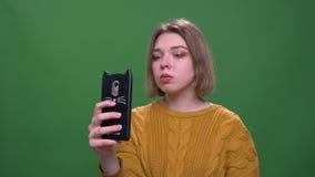 Close-upspruit van jong aantrekkelijk kort haired wijfje die die selfies op de telefoon met achtergrond nemen op groen wordt ge?s stock footage