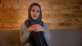 Close-upspruit van jong aantrekkelijk moslimwijfje die in hijab op een grappige show op TV letten die gelukkig terwijl het zitten stock videobeelden