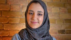 Close-upspruit van jong aantrekkelijk moslimwijfje die in hijab recht camera bekijken die cheerfully binnen bij comfortabel gliml stock footage