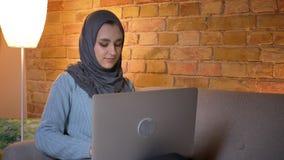 Close-upspruit van jong aantrekkelijk moslimwijfje in hijab die laptop met behulp van terwijl het zitten op de laag binnen bij co stock videobeelden