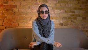 Close-upspruit van jong aantrekkelijk moslimwijfje in hijab die op een 3D film op TV letten en afstandsbediening houden terwijl stock footage