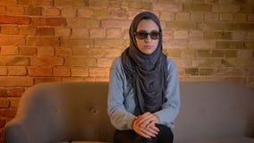 Close-upspruit van jong aantrekkelijk moslimwijfje in hijab die op een 3D verschrikkingsfilm op TV letten en een jumpscare krijge stock video