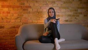 Close-upspruit van jong aantrekkelijk moslimwijfje in hijab die op TV letten en afstandsbediening houden terwijl het zitten op stock videobeelden