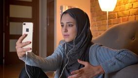 Close-upspruit van jong aantrekkelijk moslimwijfje in hijab in vibes die een videogesprek op de telefoon hebben terwijl het zitte stock footage