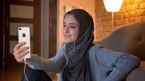 Close-upspruit van jong aantrekkelijk moslimwijfje in hijab in vibes die via videogesprek op de telefoon spreken terwijl het zitt stock videobeelden