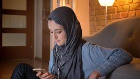 Close-upspruit van jong aantrekkelijk moslimwijfje in vibes die de telefoon met behulp van die aan muziek luisteren terwijl het z stock video