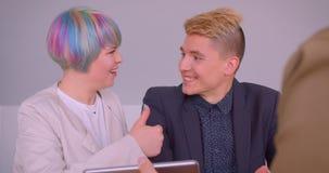 Close-upspruit van jong gelukkig hipsterpaar die een flat kopen die aan makelaar in onroerend goed en handenschudden binnen sprek stock footage
