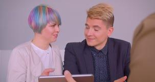 Close-upspruit van jong gelukkig hipsterpaar die een flat kopen die aan makelaar in onroerend goed en het schudden handen binnen  stock video