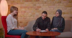 Close-upspruit van jong gelukkig moslimpaar die met een realter een nieuwe flat bespreken en een overeenkomst ondertekenen