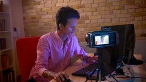 Close-upspruit van jong Indisch aantrekkelijk mannetje blogger in vibes die videospelletjes op computer levend stromen spelen stock videobeelden