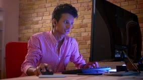 Close-upspruit van jong Indisch aantrekkelijk mannetje blogger in vibes die videospelletjes op de computer binnen in comfortabel  stock footage