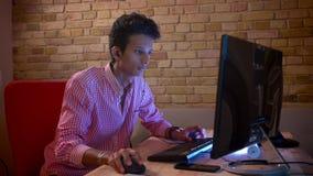 Close-upspruit van jong Indisch aantrekkelijk mannetje in vibes die videospelletjes op de computer binnen in de comfortabele flat stock video