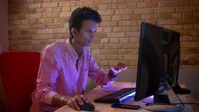 Close-upspruit van jong Indisch aantrekkelijk mannetje in vibes die videospelletjes op de computer met binnen binnen opwinding sp stock videobeelden