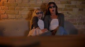 Close-upspruit van jong Kaukasisch wijfje en haar kleine dochter die op TV in 3D glazen letten die opgewekt en bang gemaakt worde stock footage