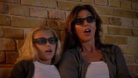 Close-upspruit van jong Kaukasisch wijfje en haar kleine dochter die op TV in 3D glazen letten die opgewekt en doen schrikken wor stock videobeelden