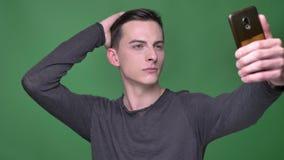 Close-upspruit van jong knap Kaukasisch mannetje die die selfies op de telefoon met achtergrond nemen op groen wordt geïsoleerd stock videobeelden