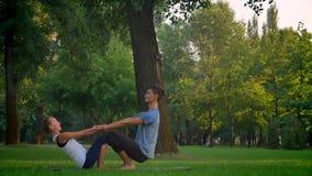 Close-upspruit van jong mannetje en wijfje die een acroyoga in het park in openlucht opleiden Man en vrouwen het gezicht van hold stock video
