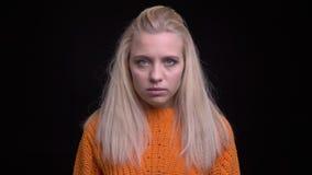Close-upspruit van jong modieus Kaukasisch wijfje die met lang blondehaar recht camera met achtergrond bekijken stock video