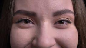 Close-upspruit van jong mooi donkerbruin vrouwelijk gezicht met haar ogen die recht camera met gezichts glimlachen bekijken stock videobeelden