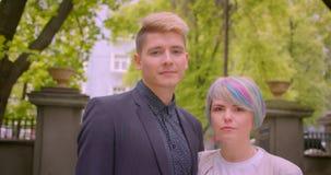 Close-upspruit van jong mooi hipsterpaar die cheerfully het koesteren spreken en camera in het park in openlucht bekijken stock video