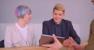 Close-upspruit van jong mooi hipsterpaar die een flat kopen die aan makelaar in onroerend goed met de tablet binnen spreken stock videobeelden