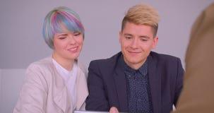 Close-upspruit van jong mooi hipsterpaar die een flat kopen die aan makelaar in onroerend goedzitting door de lijst met spreken stock videobeelden